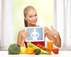 sporty woman with fruits and vegetables pointing at tablet pc
