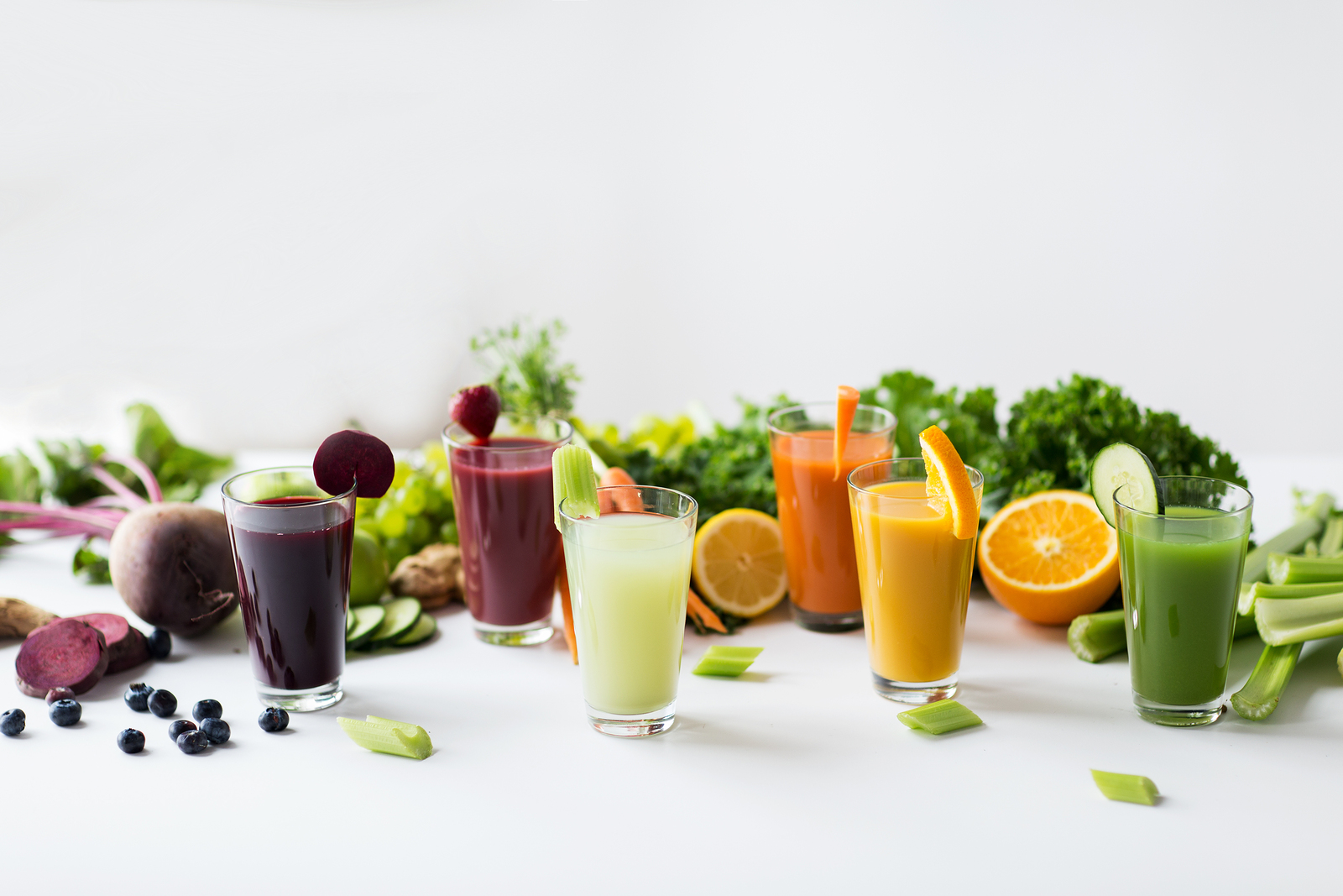healthy eating, drinks, diet and detox concept - glasses with different fruit or vegetable juices and food on table