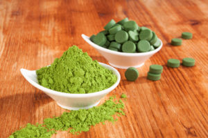 Detox. Chlorella pills and wheat grass powder in bowl on brown wooden background. Natural alternative medicine weight loss and detox.